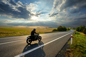 Fotobehang - Motorcycle driving on the asphalt road in rural landscape at sunset with dramatic clouds