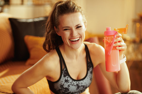 happy healthy sports woman with shaker with fitness supplements