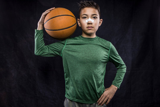 Confident young athlete holding a basketball.