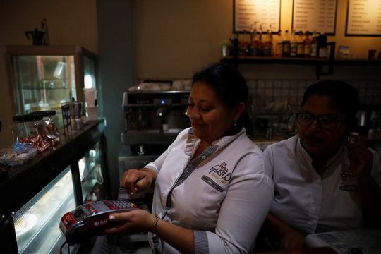 A cashier processes a customer's credit card during payment at a cafe in San Salvador