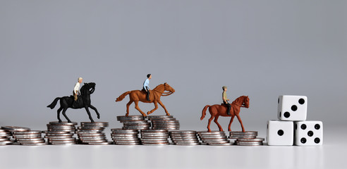 Miniature of horse rider on pile of coins. Concepts about sports gambling and probability of winning or losing.
