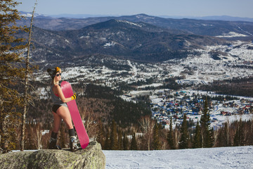 Happy Snowboarder Female wearing shirt with swimming suit standing on big rock mountain top near Christmas trees with snowboard. Hot winter sunny day