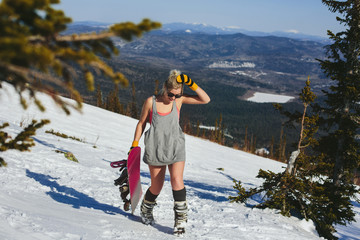 Happy Snowboarder Female wearing shirt with swimming suit walking on slope of mountain top between Christmas trees with snowboard. Hot winter sport