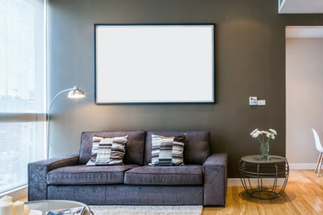 Blank frame on brown wall in living room with big window