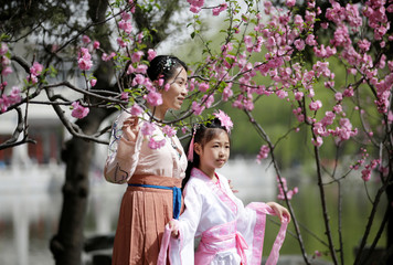 A mother and her daughter dressed in traditional costumes pose for a photo during the Qingming tomb-sweeping festival in Beijing