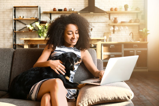 Beautiful African-American woman with cute dog working on laptop at home