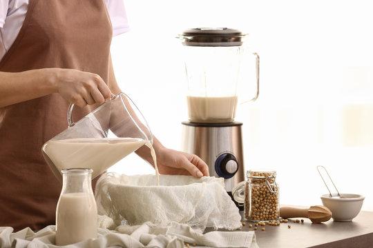 Woman making soy milk in kitchen