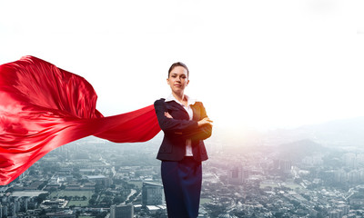 Concept of power and sucess with businesswoman superhero in big city
