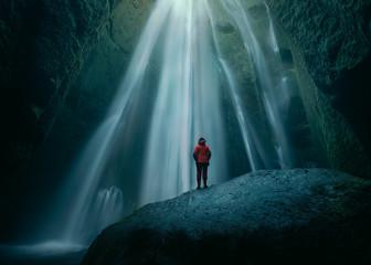 Girl on huge rock in Gljufrabui waterfall at south Iceland