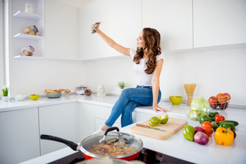 Profile side view of nice attractive lovely charming cheerful wavy-haired girl taking making selfie hot lunch meal domestic dish social influencer in light white interior room