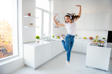 Wall Mural - Full length body size view portrait of her she nice attractive crazy childish playful girlish cheerful cheery wavy-haired girl having fun in modern light white interior style room