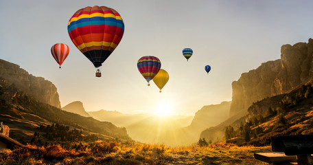 Beautiful panoramic nature landscape of countryside mountains with colorful high hot air balloons festival in summer sky. Vacation travel panorama background. Wall mural