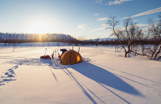Making a tent campsite during sunset in the snow of an arctic wilderness. Lapland, Sweden.