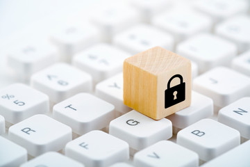 Wooden block with lock graphic on computer keyboard. Computer security concept.