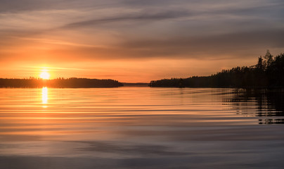 Scenic sunset landscape with water reflections and light waves at summer evening in Finland.