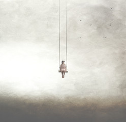 surreal image of a woman on a swing suspended in the sky