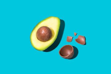 Conceptual Easter Image of Avocado with Chocolate Egg on Bright Background, Isolated Copy Space