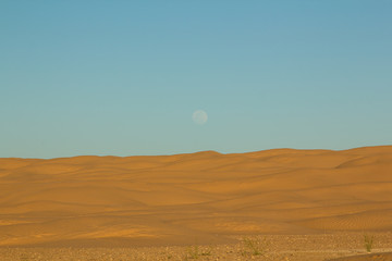 Full moon rising over the sandy dunes during an off road exploration drive through the northern Sahara in Tunisia below the city of Dousz