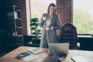 Close up photo beautiful amazing she her business lady hold white glass cup hot beverage pause break attentively reading looking notebook table sit office wearing specs formalwear checkered plaid suit