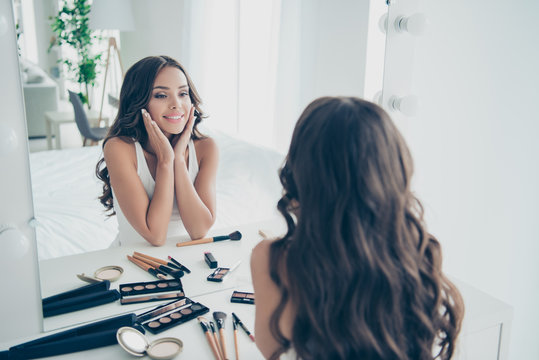 Portrait of her she nice-looking sweet tender gentle attractive lovely lovable fascinating charming cute feminine cheerful groomed wavy-haired lady looking at mirror in light white interior room