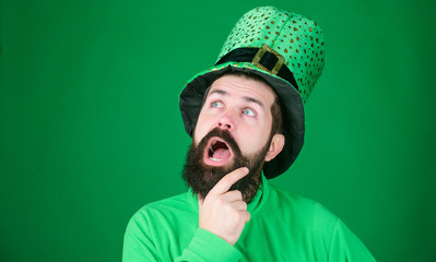Being lost in contemplation. Hipster keeping mouth open in leprechaun hat and costume. Bearded man celebrating saint patricks day. Irish man with beard wearing green. Happy saint patricks day