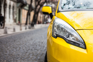 Closeup headlight of modern sport yellow car. Car exterior details over city background. Concept of expensive, sports auto