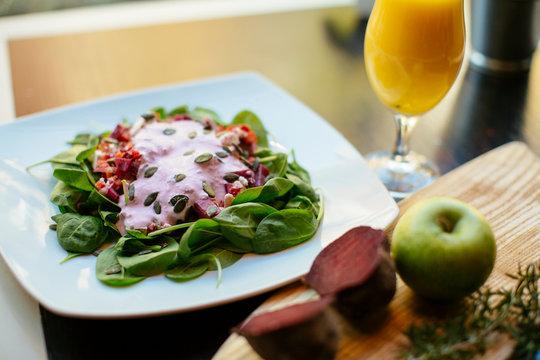 Salad with orange juice beside.
