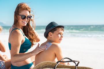 Mother applying suntan lotion on son