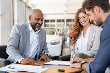Man signing contract to buy new car