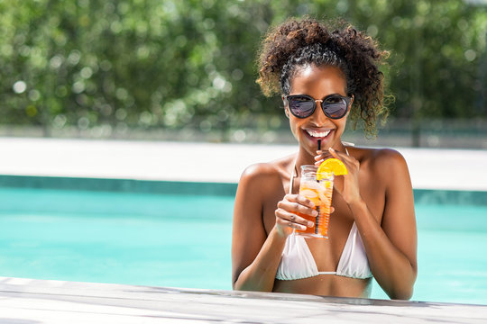 Fashion beauty woman in pool drinking cocktail