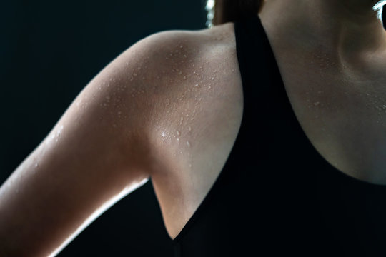 Sweaty woman after gym workout, heavy cardio or fat burning training. Sweat on wet skin. Tired fitness athlete, yoga instructor or personal trainer. Exhausted after exercise. Arm and armpit. Low key.