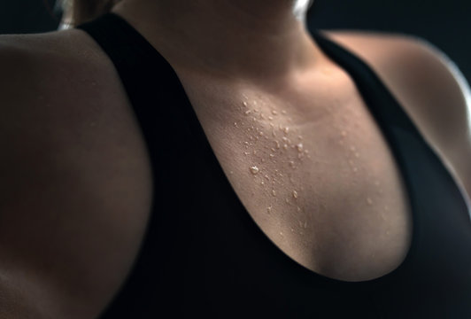 Sweat on skin. Sweaty woman after gym workout, heavy cardio or fat burning training. Yoga instructor, tired fitness athlete or personal trainer. Low key close up of wet female chest with water drops.
