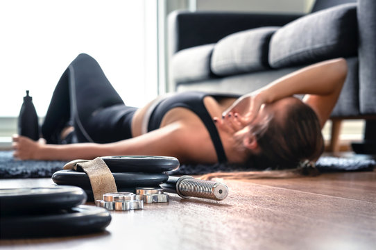 Tired after exercise and workout. Overtraining concept. Exhausted woman lying on floor breathing and resting after heavy cardio training in home gym. Sad fitness athlete. Too much working out.