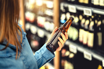 Customer buying beer in liquor store. Lager, craft or wheat beer. IPA or pale ale. Woman at alcohol shelf. Drink section and aisle in supermarket. Lady holding bottle in hand. Drink business concept. Fototapete