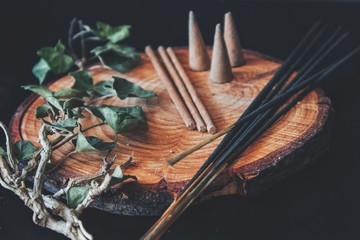 Examples of various types of incense - long black sticks, short hand made sticks and  small triangular cones. Black background, placed on a wooden plate cutting with ivy plant branch laying next to it