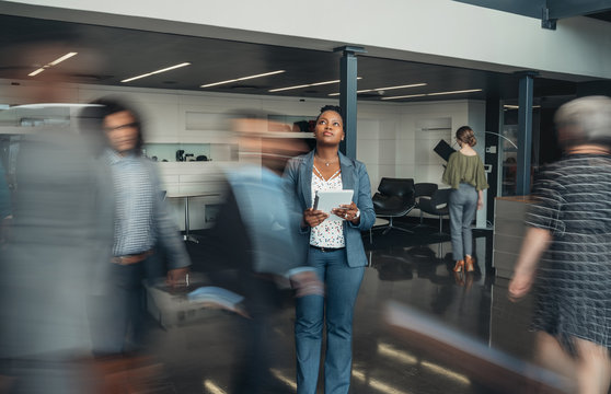 Beautiful black african business woman standing in a busy lobby of an office looking upwards, holding a tablet with people walking past in a blur