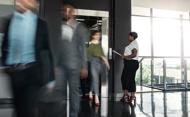Black african business woman standing with paperwork, waiting to enter a busy elevator lift. With people walking out in a blur, showing motion. Wall mural