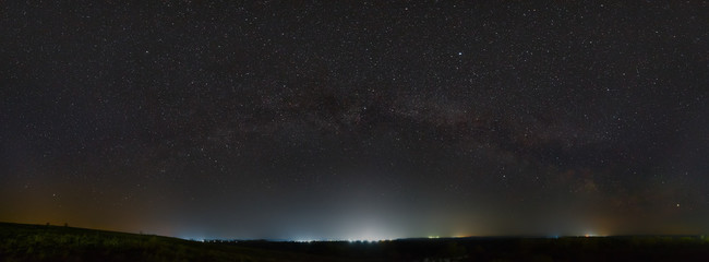 Stars of the Milky Way in the night sky. Light pollution from street lamps above the horizon. Fotomurales