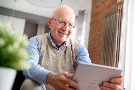 Senior man using digital tablet in living room