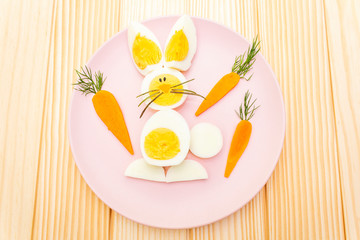 Easter bunny (rabbit) eggs children (kids) food concept. With carrot on rosy (pink) plate. Wooden background, top view