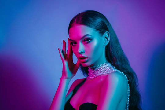 High fashion model in colorful bright neon lights posing at studio. Portrait of beautiful girl with trendy glowing make-up. Art design vivid style.