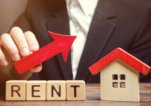 Wooden blocks with the word Rent, house and up arrow. The concept of the high cost of rent for an apartment or home. Interest rates are rising. Real estate market. Increased demand for rental property