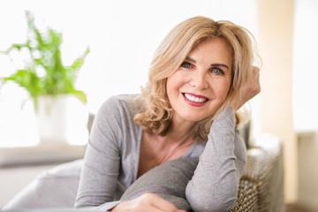 Portrait einer attraktiven älteren Frau zuhause auf der Couch, best ager