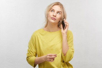 Portrait of beautiful blond woman in yellow casual outfit talking mobile phone with thoughtful look, girl holding phone, look upper left corner and thinking in white studio