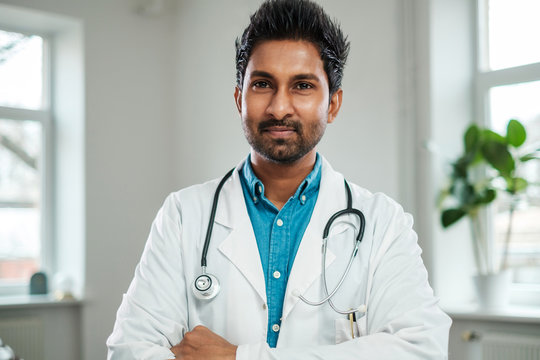 Indian doctor with stethoscope around neck in his office
