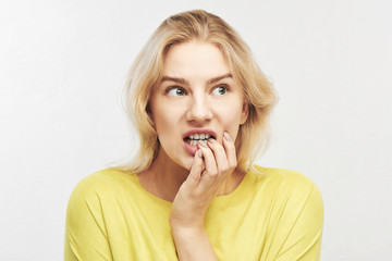 Young female blonde worried and bites her nails with expression of fear emotion on face. Stress from studying, working, relationships, illness isolated on white background