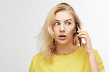 Portrait of shocked girl with open mouth talking mobile phone on white background with free advertising space. Woman in yellow casual outfit hears something amazing, she confused