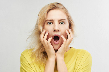 Woman in horror holds head with hands and screams of fear, anger and surprise isolated on white background. Something terrible and unexpected happened, expressive emotions