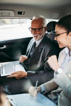Good looking senior business man and his young woman colleague or coworker sitting on backseat in luxury car. They talking, smiling and using laptop and smart phones.