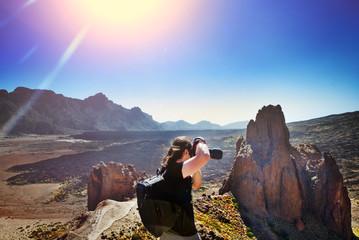 Fotógrafo en acción con su equipo durante la puesta de sol en una montaña rocosa. Concepto de viajes de aventura. Tenerife